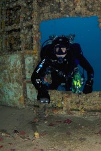 Diver swims in a sunken ship